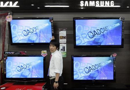 An electronics shop salesperson sells flat screen TVs of Samsung Electronics displayed at a shop in Seoul